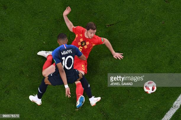 France's forward Kylian Mbappe vies for the ball with Belgium's defender Jan Vertonghen as he eyes the ball during the Russia 2018 World Cup...