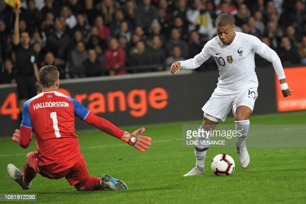 TOPSHOT France's forward Kylian Mbappe vies with Iceland's goalkeeper Hannes Thor Halldorsson during the friendly football match between France and...