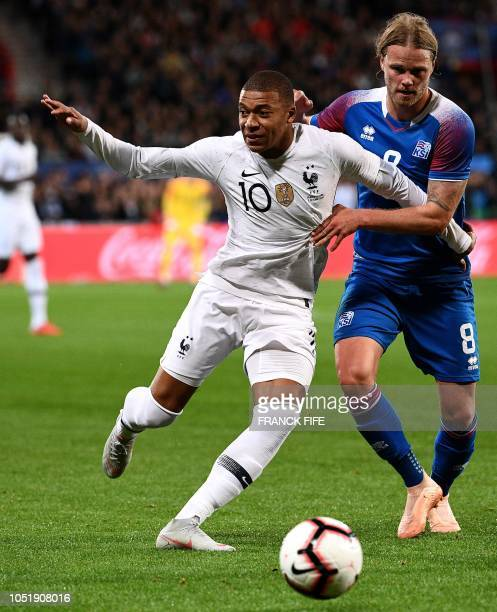 France's forward Kylian Mbappe vies with Iceland's midfielder Birkir Bjarnason during the friendly football match between France and Iceland at the...