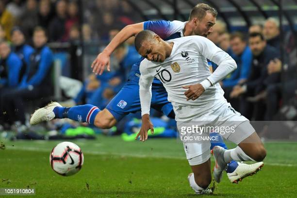 France's forward Kylian Mbappe vies with Iceland's midfielder Runar Mar Sigurjonsson during the friendly football match between France and Iceland at...