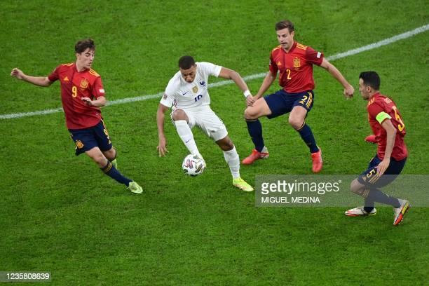 France's forward Kylian Mbappe vies with Spain's midfielder Gavi , Spain's midfielder Sergio Busquets and Spain's defender Cesar Azpilicueta during...