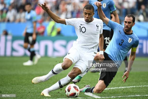 France's forward Kylian Mbappe vies with Uruguay's defender Diego Godin during the Russia 2018 World Cup quarterfinal football match between Uruguay...