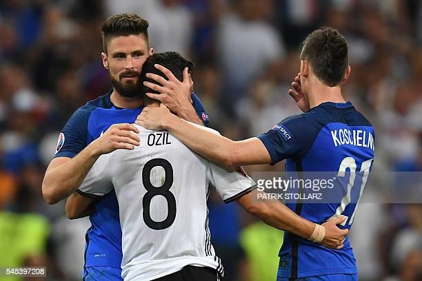 TOPSHOT France's forward Olivier Giroud and France's defender Laurent Koscielny consol Germany's midfielder Mesut Oezil after France beat Germany 20...
