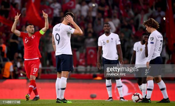 TOPSHOT France's Forward Olivier Giroud and France's forward Antoine Griezmann react after Turkey's scoring their second goal during the Euro 2020...