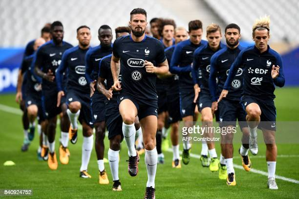 France's forward Olivier Giroud and France's forward Antoine Griezmann run with teammates during a training session on August 30 2017 at the Stade de...