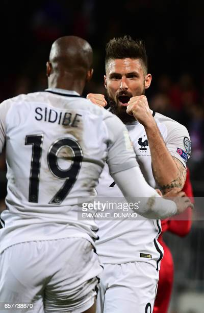 France's forward Olivier Giroud celebrates with France's defender Djibril Sidibe after scoring during the World Cup 2018 football qualification match...