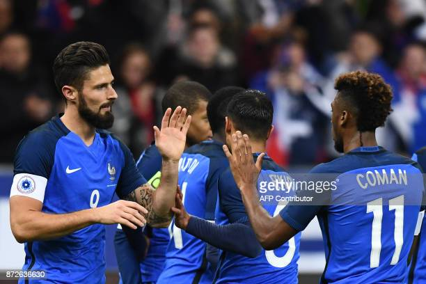 France's forward Olivier Giroud celebrates with teammates after scoring a goal during the friendly football match between France and Wales at the...
