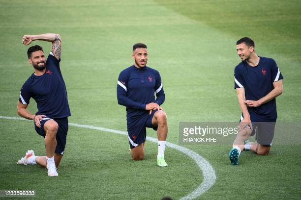 France's forward Olivier Giroud, France's midfielder Corentin Tolisso and France's defender Clement Lenglet take part in a MD-1 training session at...