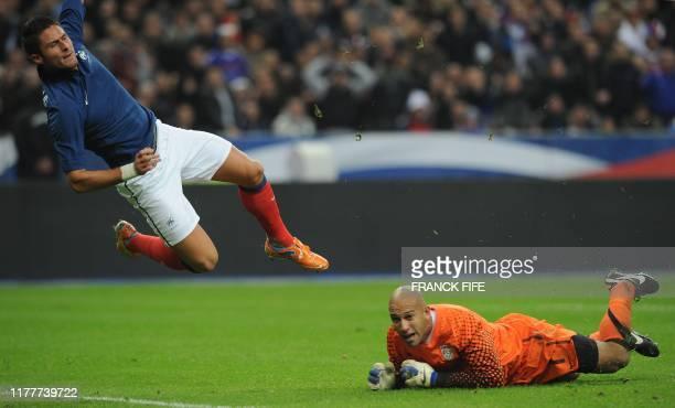 France's forward Olivier Giroud goes airborne eyed by US goalkeeper Tim Howard during the friendly football match France v USA on November 11 2011 at...