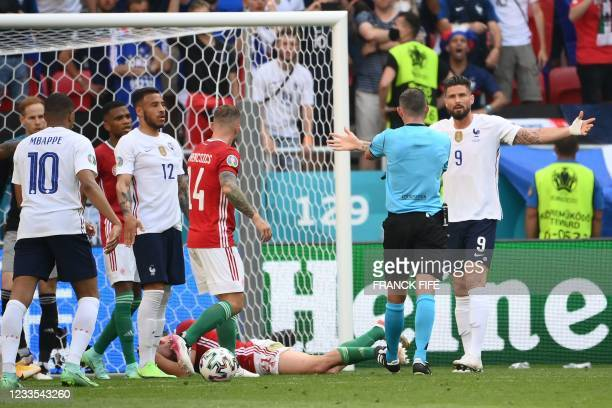 France's forward Olivier Giroud has words with the referee during the UEFA EURO 2020 Group F football match between Hungary and France at Puskas...