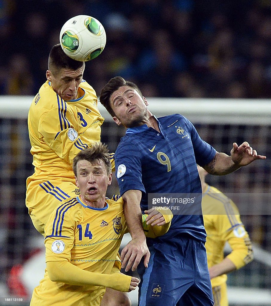 France's forward Olivier Giroud (R) heads the ball with Ukraine's defender Yevhen Khacheridi (top -L) and midfielder Ruslan Rotan (L) during the 2014 FIFA World Cup qualifying play-off first leg football match between Ukraine and France at the Olympic Stadium in Kiev on November 15, 2013.