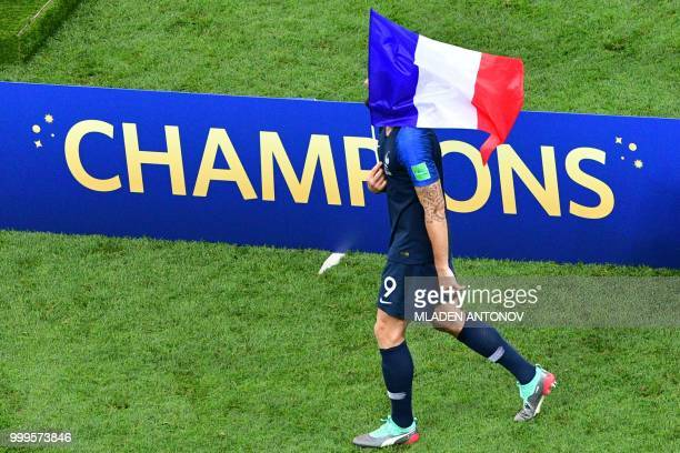 TOPSHOT France's forward Olivier Giroud holds a French flag as he celebrates after the Russia 2018 World Cup final football match between France and...