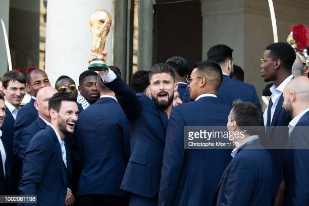 France's forward Olivier Giroud holds the trophy as he arrives at a reception for the French national football team after they won the Russia 2018...