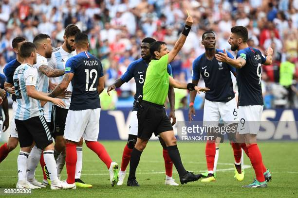 France's forward Olivier Giroud is shown a yellow card by Irani referee Alireza Faghani during the Russia 2018 World Cup round of 16 football match...