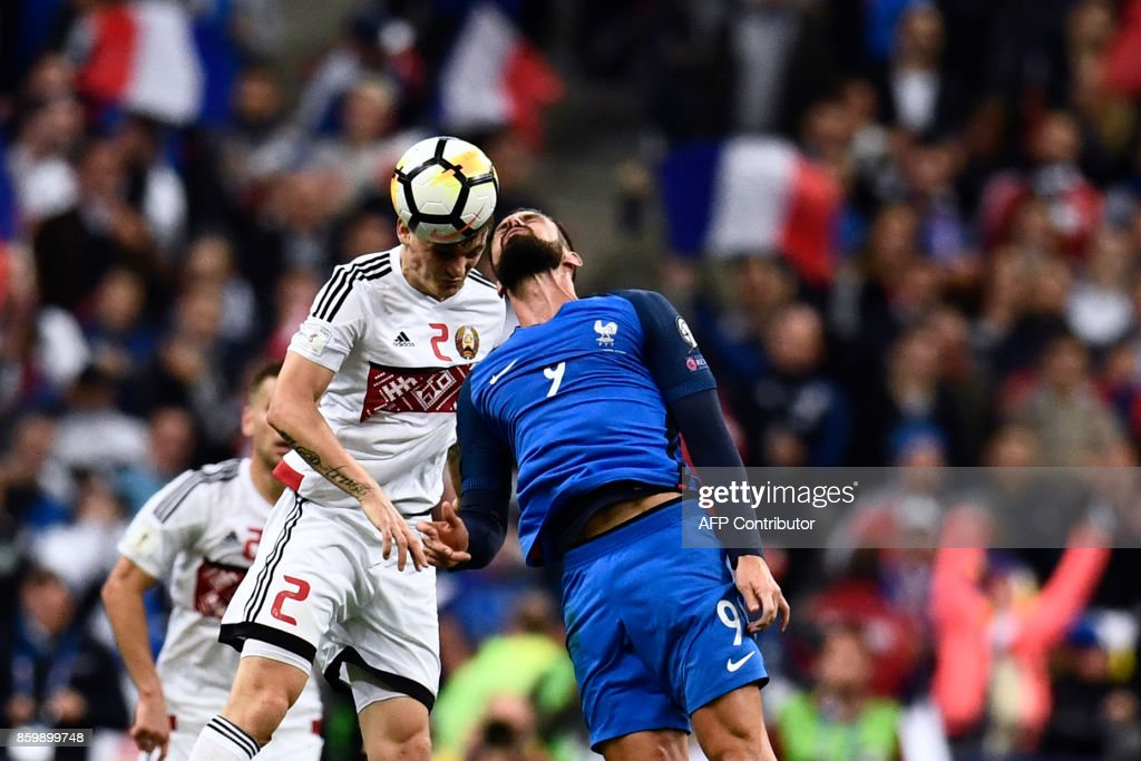 TOPSHOT - France's forward Olivier Giroud (R) jumps for the ball with Belarus' midfielder Stanislav Dragun during the FIFA World Cup 2018 qualification football match between France and Belarus at the Stade de France in Saint-Denis, north of Paris, on October 10, 2017. /