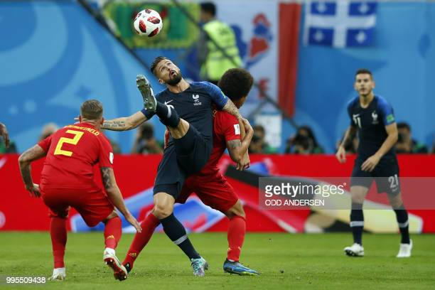France's forward Olivier Giroud kicks the ball as he vies with Belgium's defender Toby Alderweireld during the Russia 2018 World Cup semi-final...