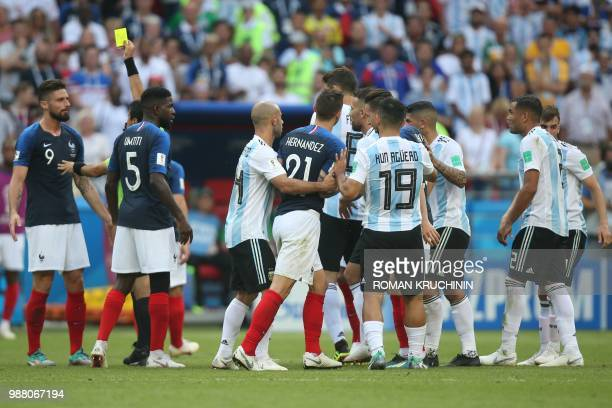 France's forward Olivier Giroud receives a yellow card from Iranian referee Alireza Faghani as France's and Argentina's players scuffle during the...