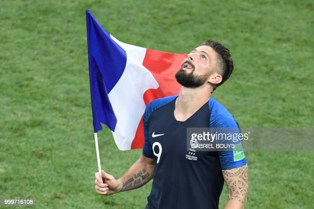France's forward Olivier Giroud runs with the French national flag as he celebrates at the end of the Russia 2018 World Cup final football match...