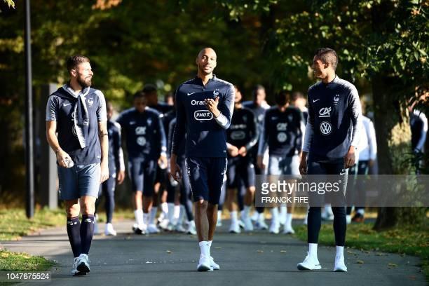 France's forward Olivier Giroud speaks with France's midfielder Steven N'zonzi and France's defender Raphael Varane before a training session in...