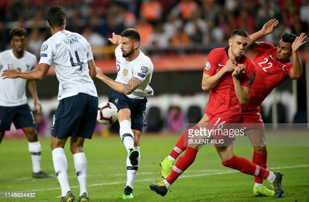 France's Forward Olivier Giroud vies with Turkey's defender Merih Demiral and Turkey's defender Kaan Ayhan during the Euro 2020 football...