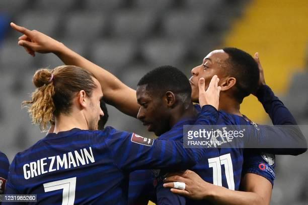 France's forward Ousmane Dembele celebrates with France's forward Antoine Griezmann and France's forward Anthony Martial teammates after scoring a...