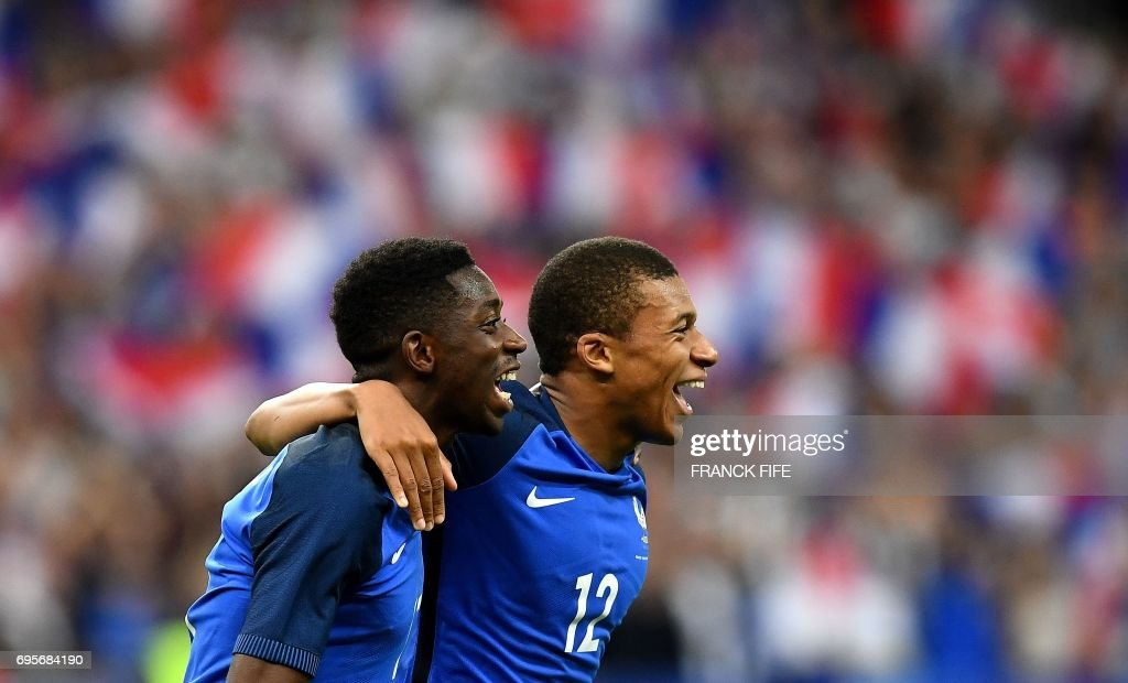 France's forward Ousmane Dembele (L) is congratulated by France's midfielder Kylian Mbappe following his goal during the international friendly football match between France and England at The Stade de France Stadium in Saint-Denis near Paris on June 13, 2017. /
