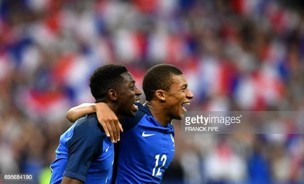 France's forward Ousmane Dembele is congratulated by France's midfielder Kylian Mbappe following his goal during the international friendly football...