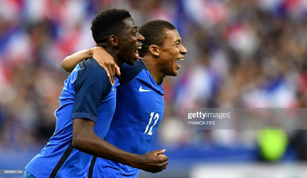 TOPSHOT - France's forward Ousmane Dembele (L) is congratulated by France's midfielder Kylian Mbappe following his goal during the international friendly football match between France and England at The Stade de France Stadium in Saint-Denis near Paris on June 13, 2017. /