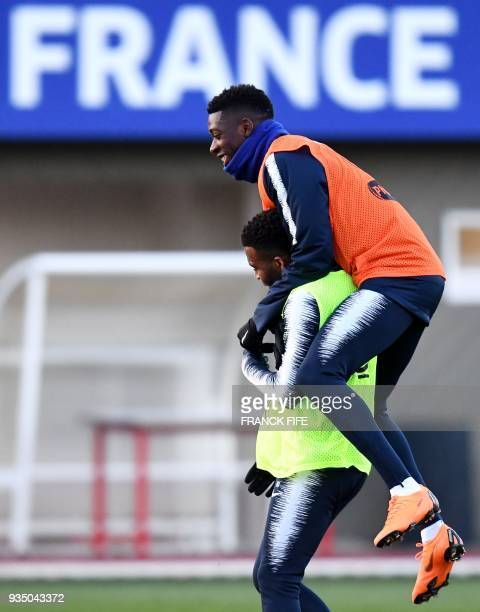 France's forward Ousmane Dembele jokes with France's midfielder Thomas Lemar during a training session in Clairefontaine en Yvelines on March 20 as...