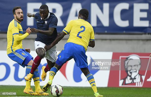 France's forward PaulGeorges Ntep challenges Sweden's defender Joseph Baffo and Sweden's midfielder Imad Khalili during the 2015 UEFA European...
