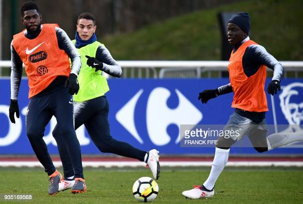 France's forward Wissam Ben Yedder vies with France's defender Samuel Umtiti next to France's midfielder N'Golo Kante during a training session in...