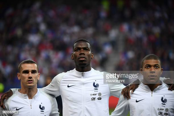 France's foward Antoine Griezmann France's midfielder Paul Pogba and France's foward Kylian Mbappe stand in a line before the friendly football match...