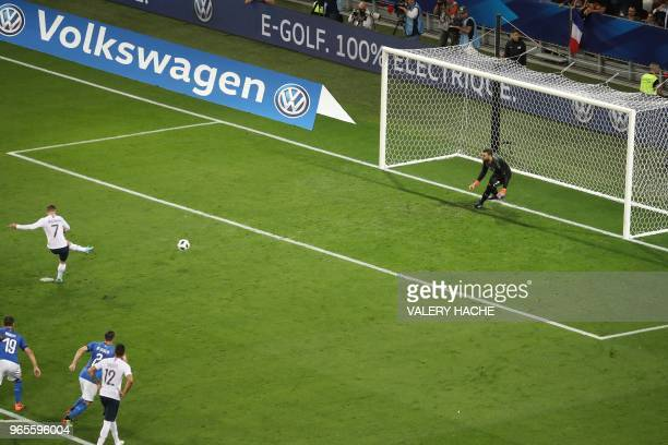 France's foward Antoine Griezmann shoots and scores a penalty kick past Italy's goalkeeper Salvatore Sirigu during the friendly football match...
