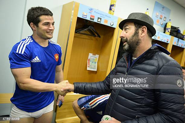 France's fullback Brice Dulin shakes hands with French actor Kad Merad in the locker room after his defeat in the Six Nations rugby union match...