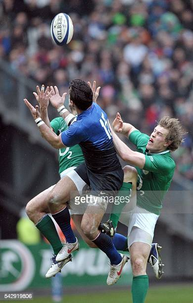 France's fullback Clement Poitrenaud jumps to catch the ball with Ireland wing Andrew Trimble during the rugby union 6 Nations tournament match...