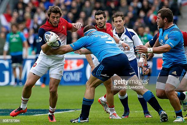 France's fullback Maxime Medard is tackled by Italy's prop Lorenzo Cittadini during the Six Nations international rugby union match between France...