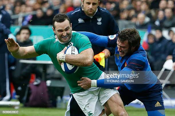 France's fullback Maxime Medard tackles Ireland's fullback Dave Kearney during the Six Nations international rugby union match between France and...