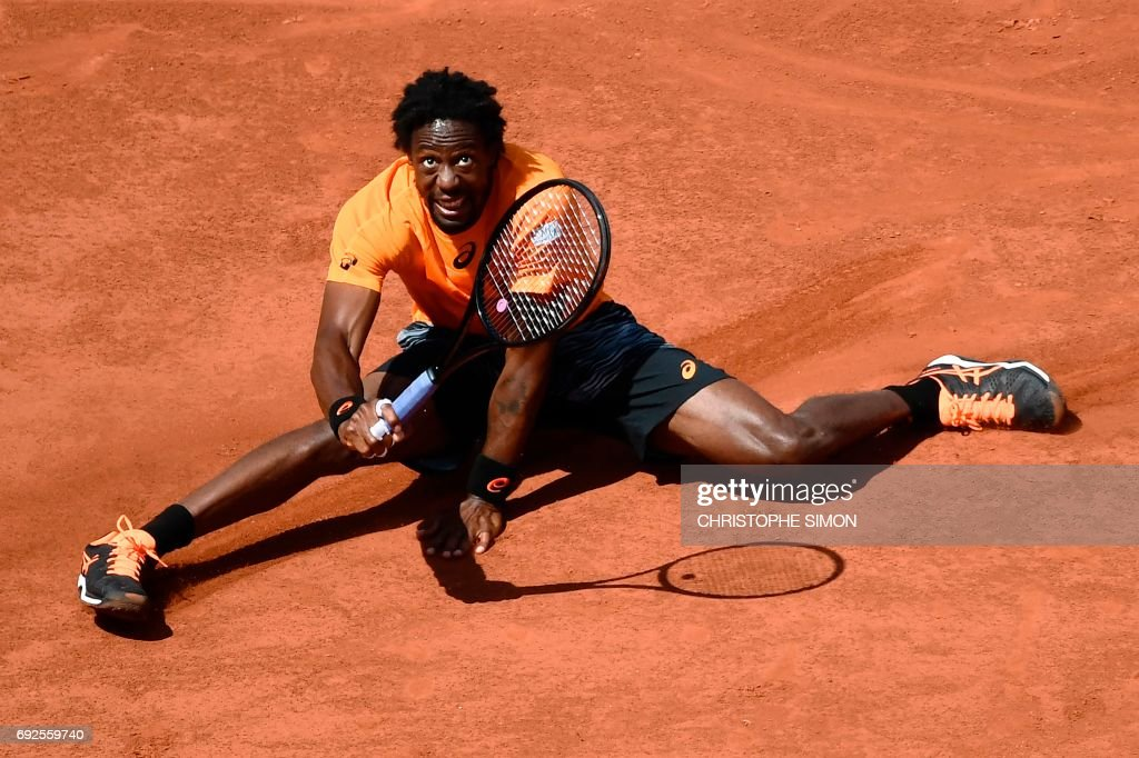 France's Gael Monfils falls down after returning the ball to Switzerland's Stanislas Wawrinka during their tennis match at the Roland Garros 2017 French Open on June 5, 2017 in Paris. /