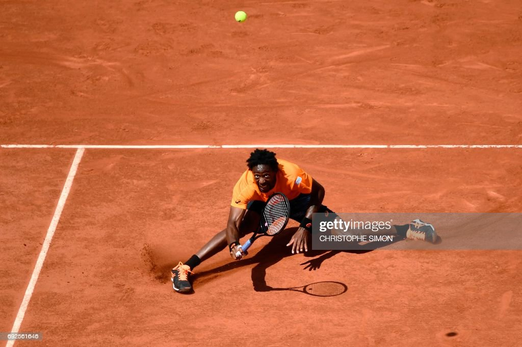 TOPSHOT - France's Gael Monfils falls down after returning the ball to Switzerland's Stanislas Wawrinka during their tennis match at the Roland Garros 2017 French Open on June 5, 2017 in Paris. /