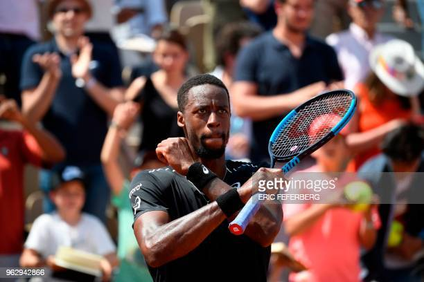 France's Gael Monfils gestures as he celebrates after victory over compatriot Elliot Benchetrit in their men's singles first round match on day one...