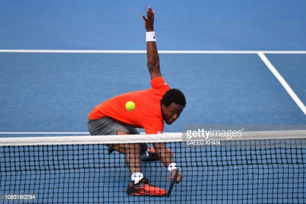 France's Gael Monfils hits a return against Taylor Fritz of the US during their men's singles match on day three of the Australian Open tennis...