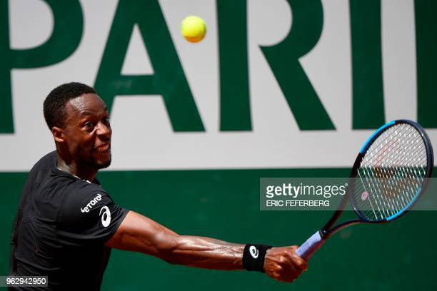 France's Gael Monfils plays a backhand return to compatriot Elliot Benchetrit during their men's singles first round match on day one of The Roland...