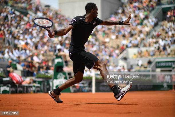 France's Gael Monfils plays a return to compatriot Elliot Benchetrit during their men's singles first round match on day one of The Roland Garros...