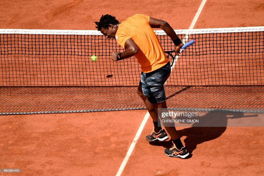 France's Gael Monfils reacts after hurting his ankle as he plays against Switzerland's Stanislas Wawrinka during their tennis match at the Roland Garros 2017 French Open on June 5, 2017 in Paris. /