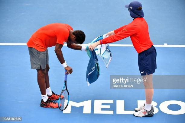 France's Gael Monfils receives a towel from a ballboy as he plays against Taylor Fritz of the US during their men's singles match on day three of the...