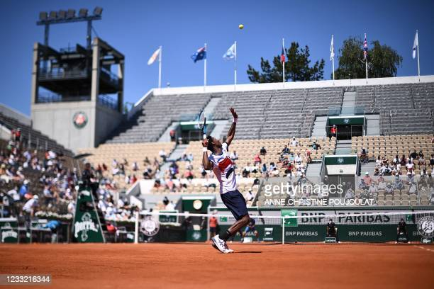 France's Gael Monfils serves the ball to Spain's Albert Ramos-Vinolas during their men's singles first round tennis match on Day 3 of The Roland...