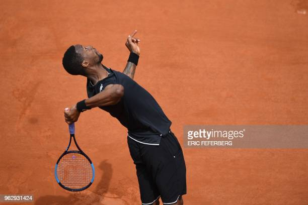 France's Gael Monfils serves to compatriot Elliot Benchetrit during their men's singles first round match on day one of The Roland Garros 2018 French...