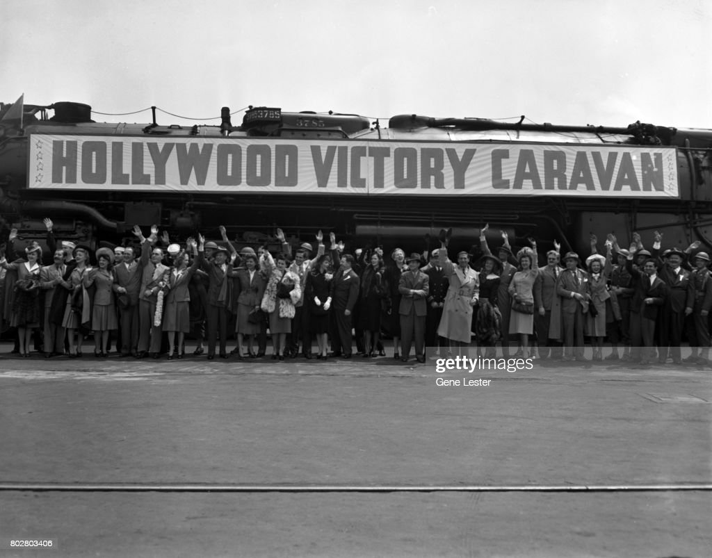 Frances Gifford;Jerry Colonna;Karin Booth;Paye McKenzie;Edward Arnold;Pat O'Brien;Marie McDonald;Bert Lahr;Frances Langford;Joan Bennett;Desi Arnaz;Claudette Colbert;Frank McHugh;Eleanor Powell;Charlotte Greenwood;Stan Laurel;Joan Blondell;Cary Grant;Rise Stevens;Jean Hersholt;Charles Boyer;Elyse Knox;Oliver Hardy performing at the LA train station aka Union Station as part of the Hollywood Victory Caravan which was a group of stars who toured 13 US cities to raise funds for Army and Navy relief during WW2 in March 1942.