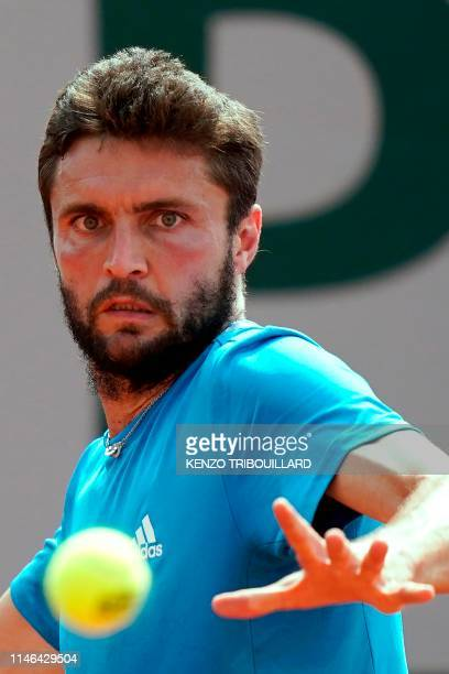 France's Gilles Simon eyes the ball as he returns the ball to Ukraine's Sergiy Stakhovsky during their men's singles first round match on day two of...