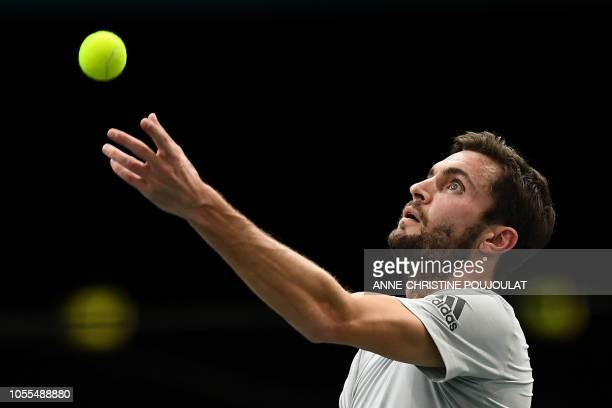 France's Gilles Simon eyes the ball as he serves to France's Lucas Pouille during their men's singles first round match on day two of the ATP World...